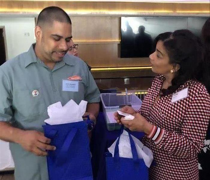 Male Employee and Female each Holding Blue Bags