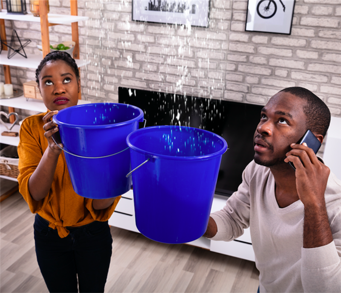 A couple holding buckets since the ceiling is leaking while on the phone with a plumber.