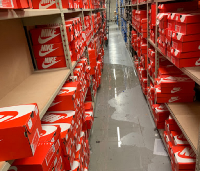 Shoe boxes in warehouse, water on floor